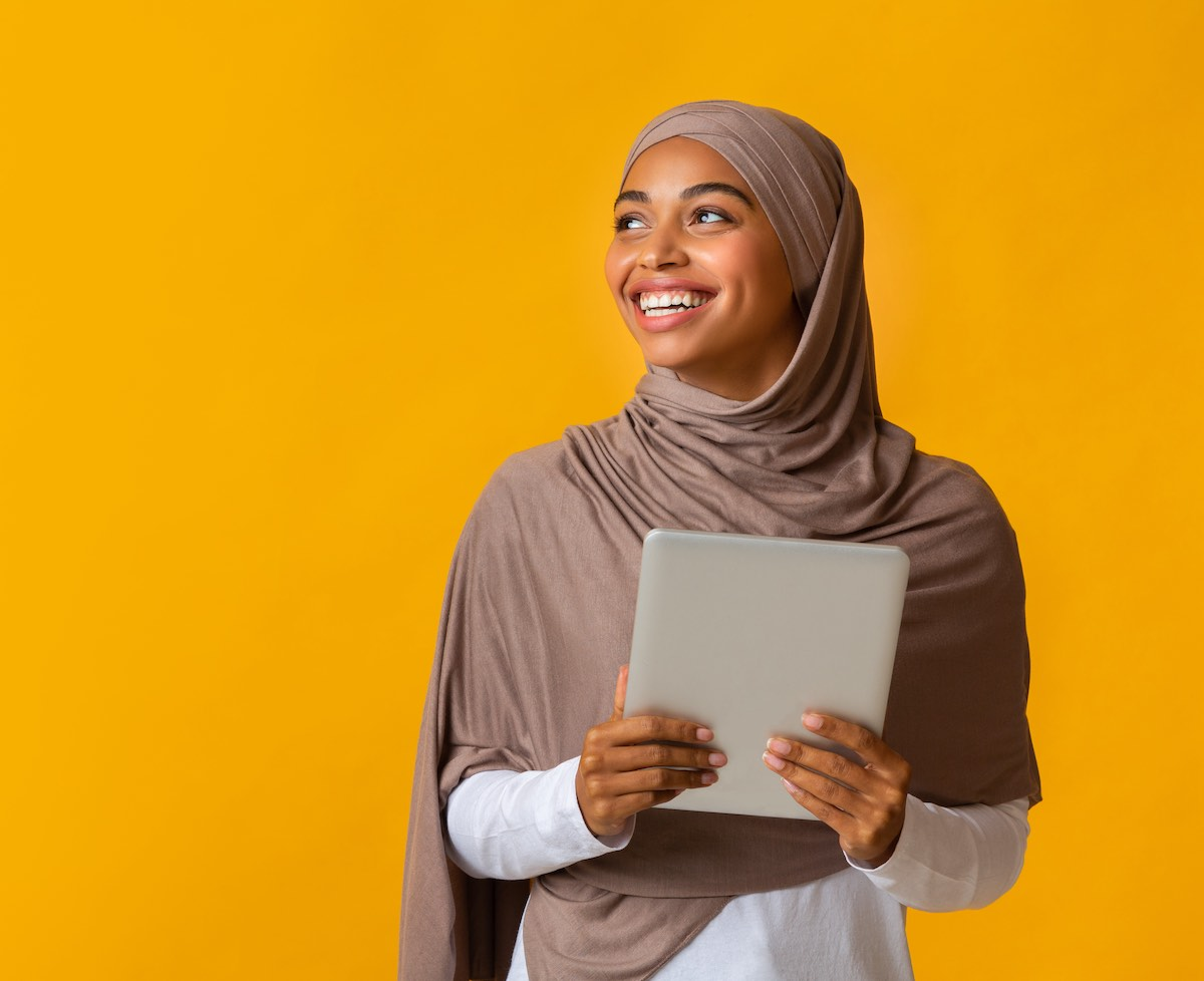 Images shows a smiling black muslim girl in hijab holding digital tablet