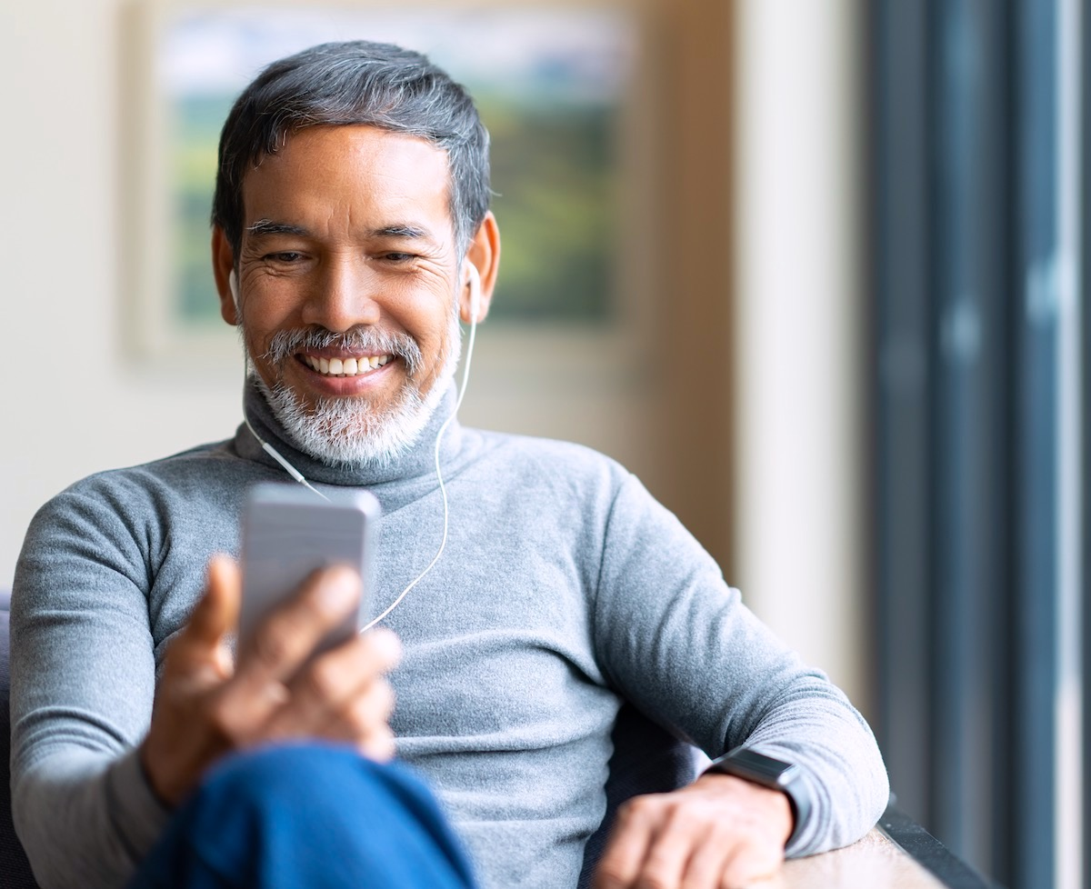 Image shows a man smiling while making a call on his phone