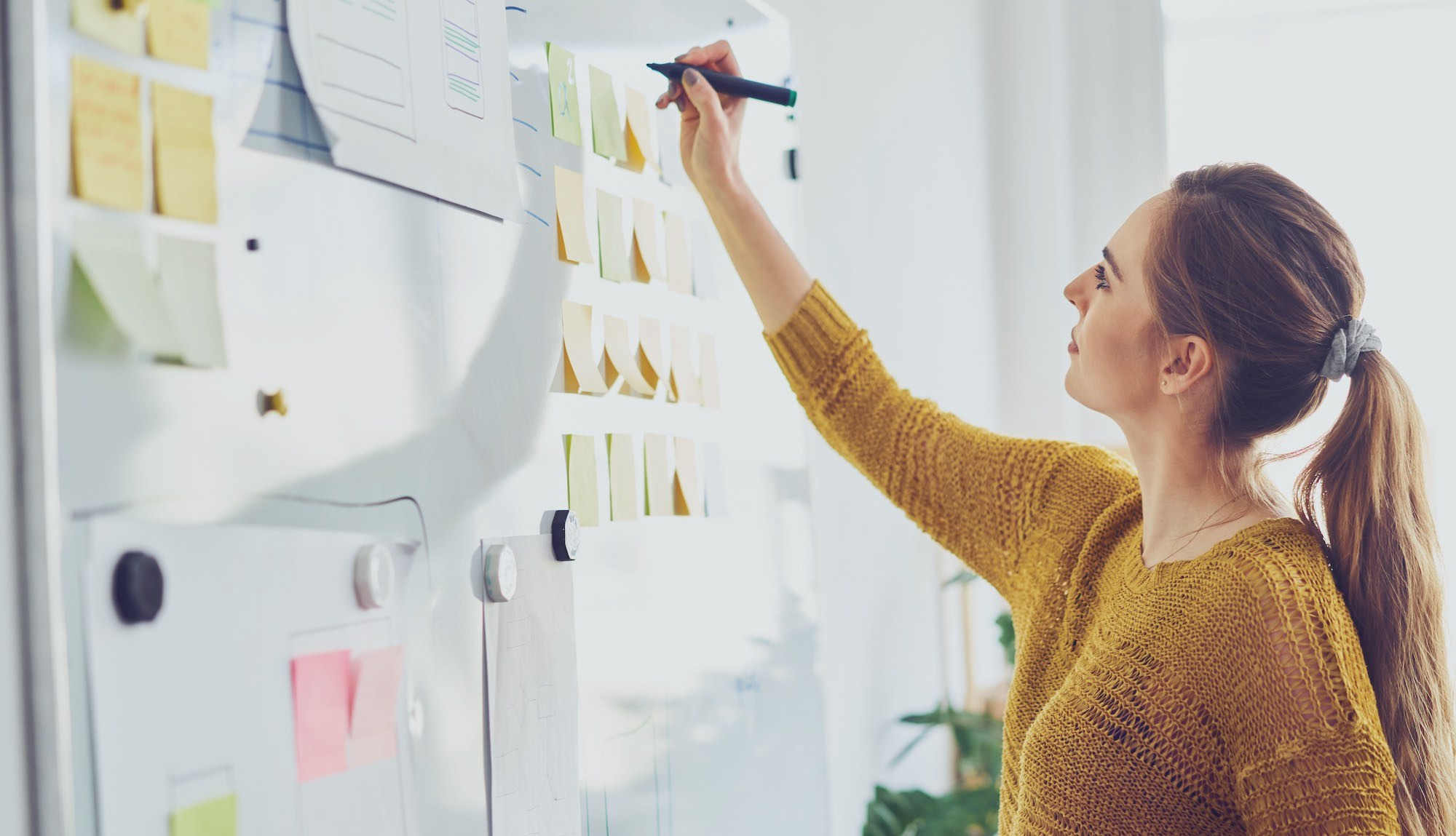 Image shows woman at whiteboard in a planning meeting