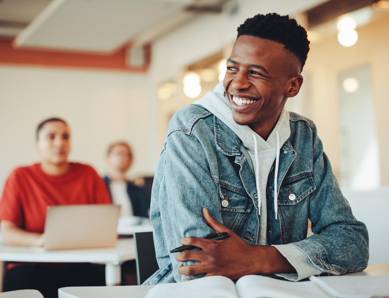 Image shows a smiling student in a classroom setting